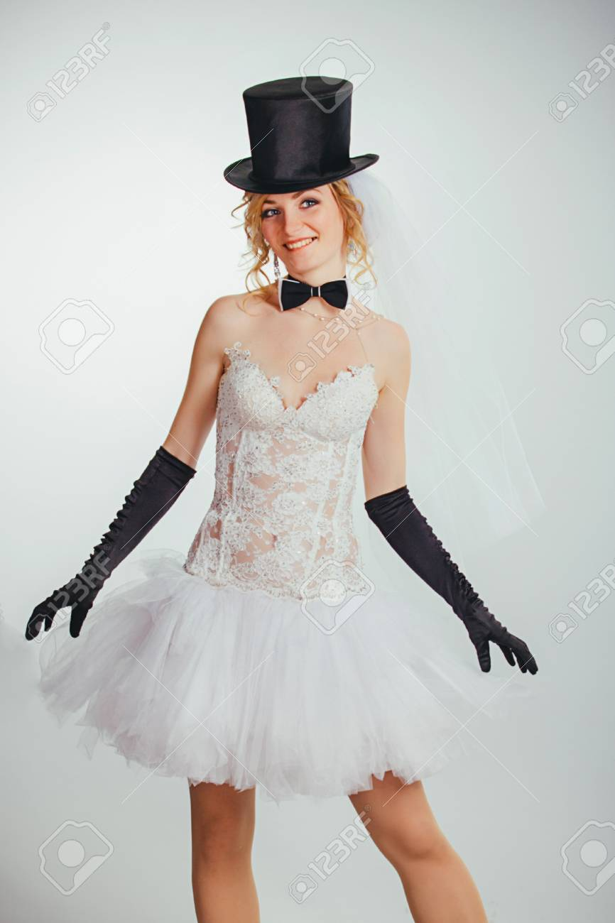 Stock Photo - young beautiful blonde bride in tophat with veil and stylish wedding  dress with long black gloves f6794b5d4ba