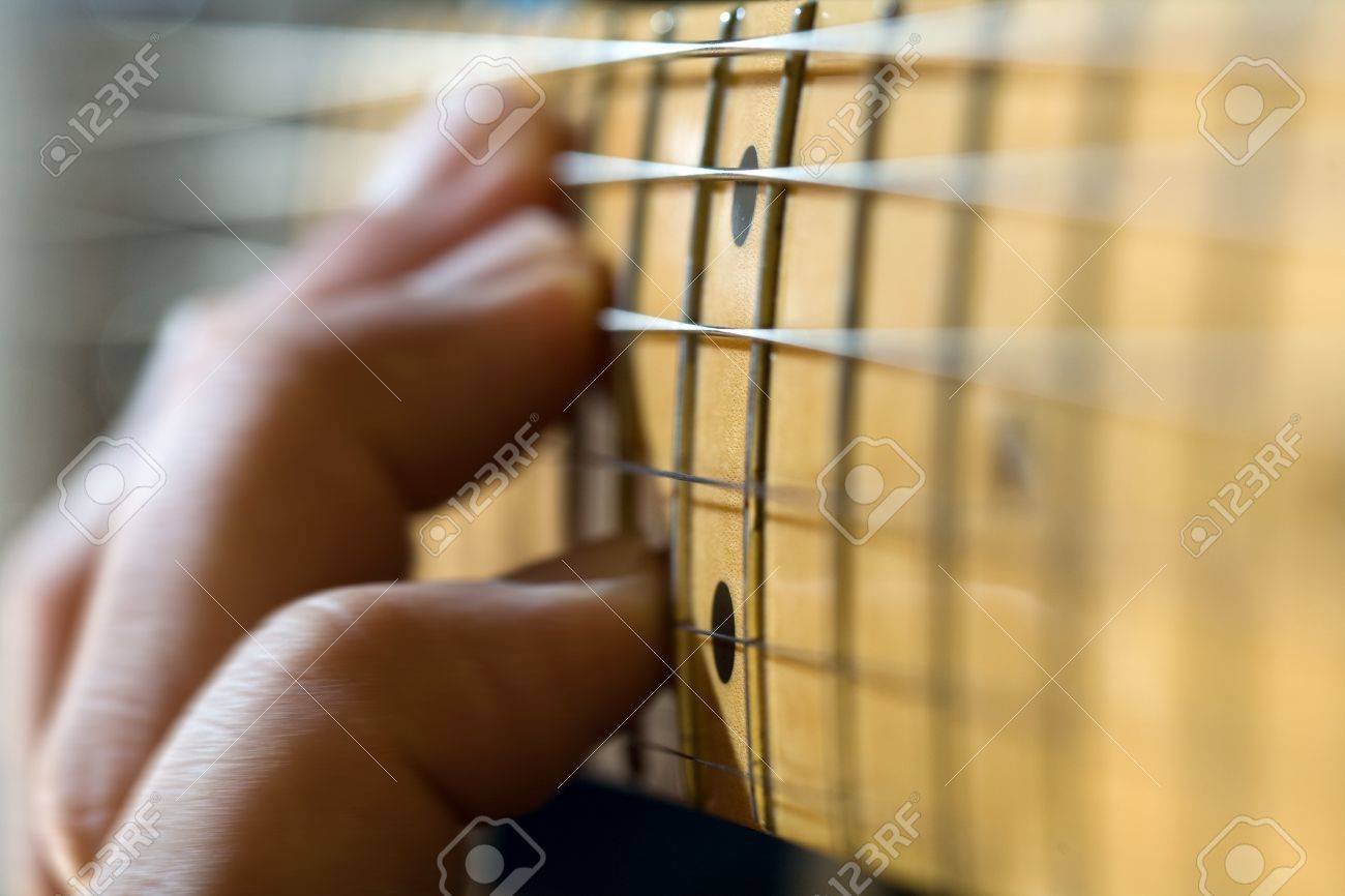 close-up of electric guitar fretboard with hand sliding a chord up the neck Stock Photo - 17980406