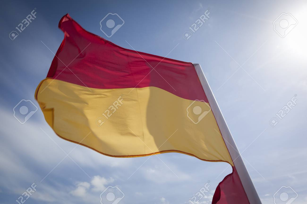 Woolacombe, United Kingdom - May 19, 2011: Close-up of a red and yellow safety flag fluttering in the wind against a bright blue sky. The flag is used by lifeguards to mark the safe swimming area. Stock Photo - 18614588