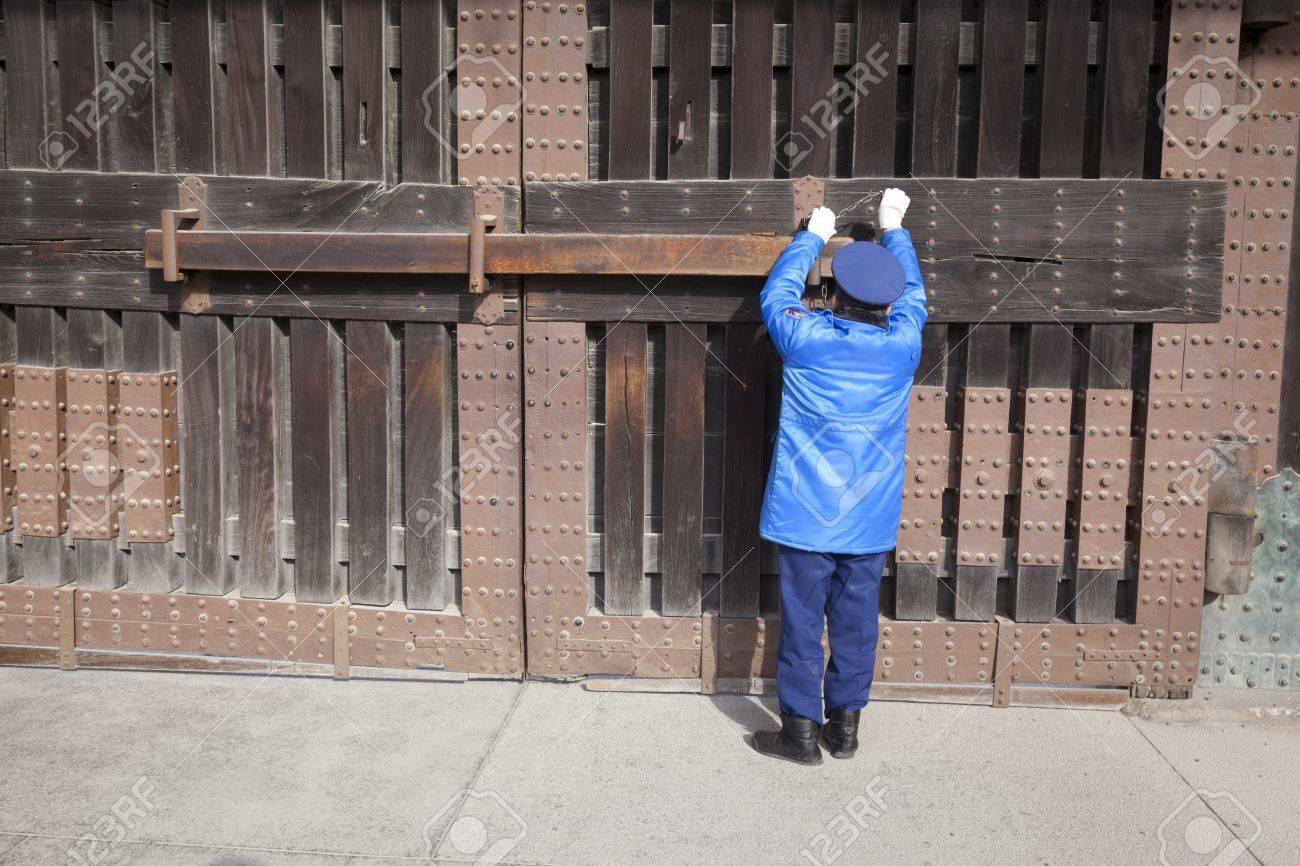 Kyoto, Japón - 19 de marzo de 2012: Un guardia de seguridad en un uniforme azul bloquea la gran puerta de entrada de madera de Nijo castle en Kyoto, Japón. Foto de archivo - 18614605