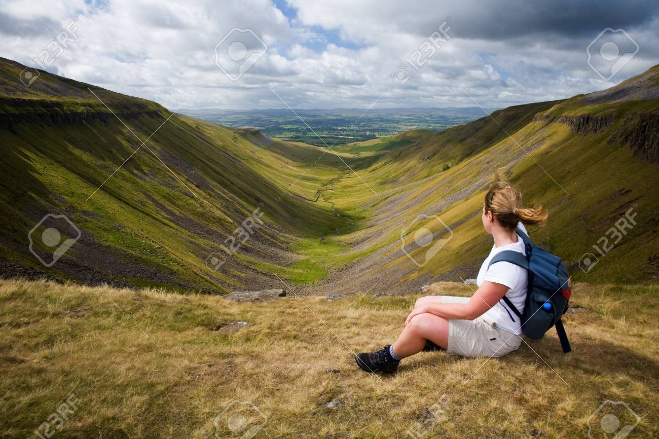On a windy day a walker sits enjoying the view from a Cumbrian beauty spot called High Cup Nick in England, UK Stock Photo - 24835856