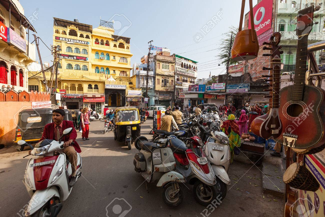 busy restaurant scene. stock photo - udaipur, india january 16, 2015 : busy street scene in jagdish chowk, a central town square udaipur filled with mopeds, rickshaws, restaurant r