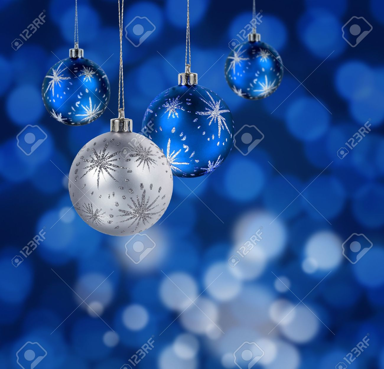 Blue And Silver Christmas Balls Hanging Against Blue Light Spots ...