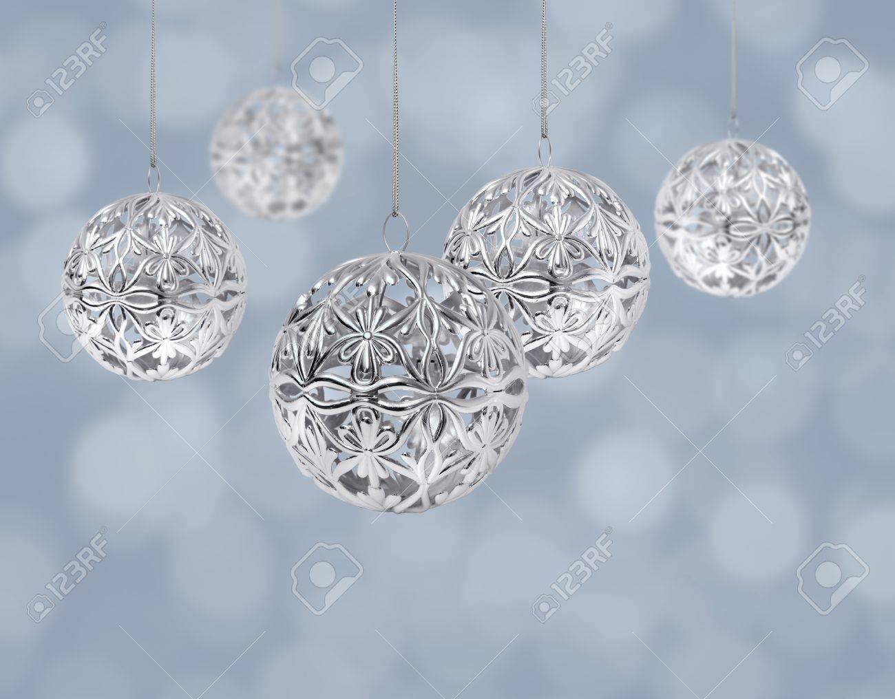 Shiny silver Christmas balls hanging on light blue background Stock Photo - 8331447