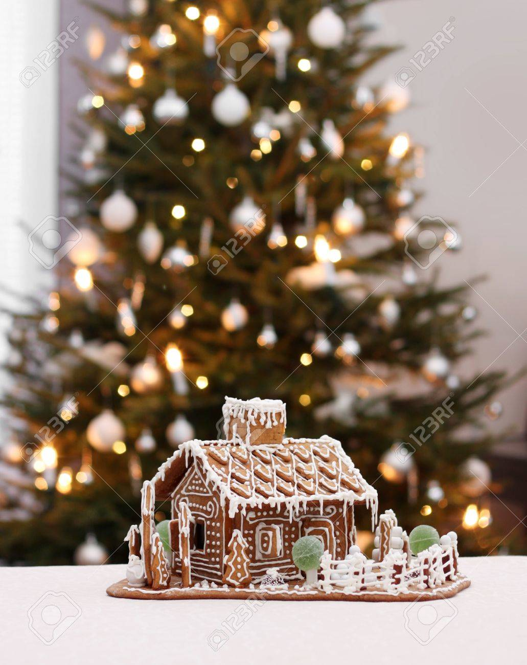 Gingerbread Cottage House On Real Christmas Tree Background Stock Photo