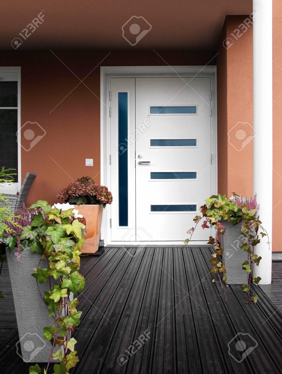 Entrée de maison en pierre moderne porte blanche avec fenêtres