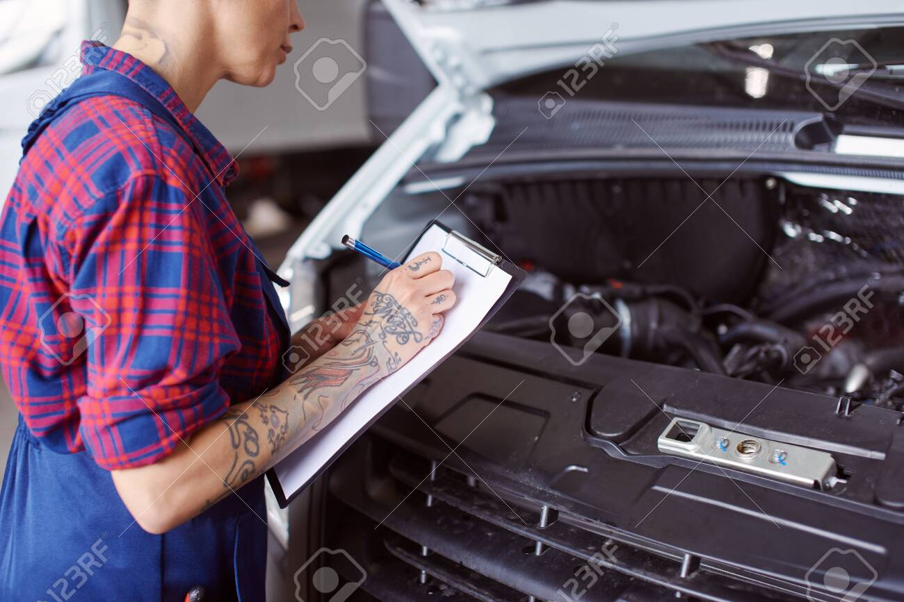Automechanic makes a list of problems needed to be checked. - 128911951