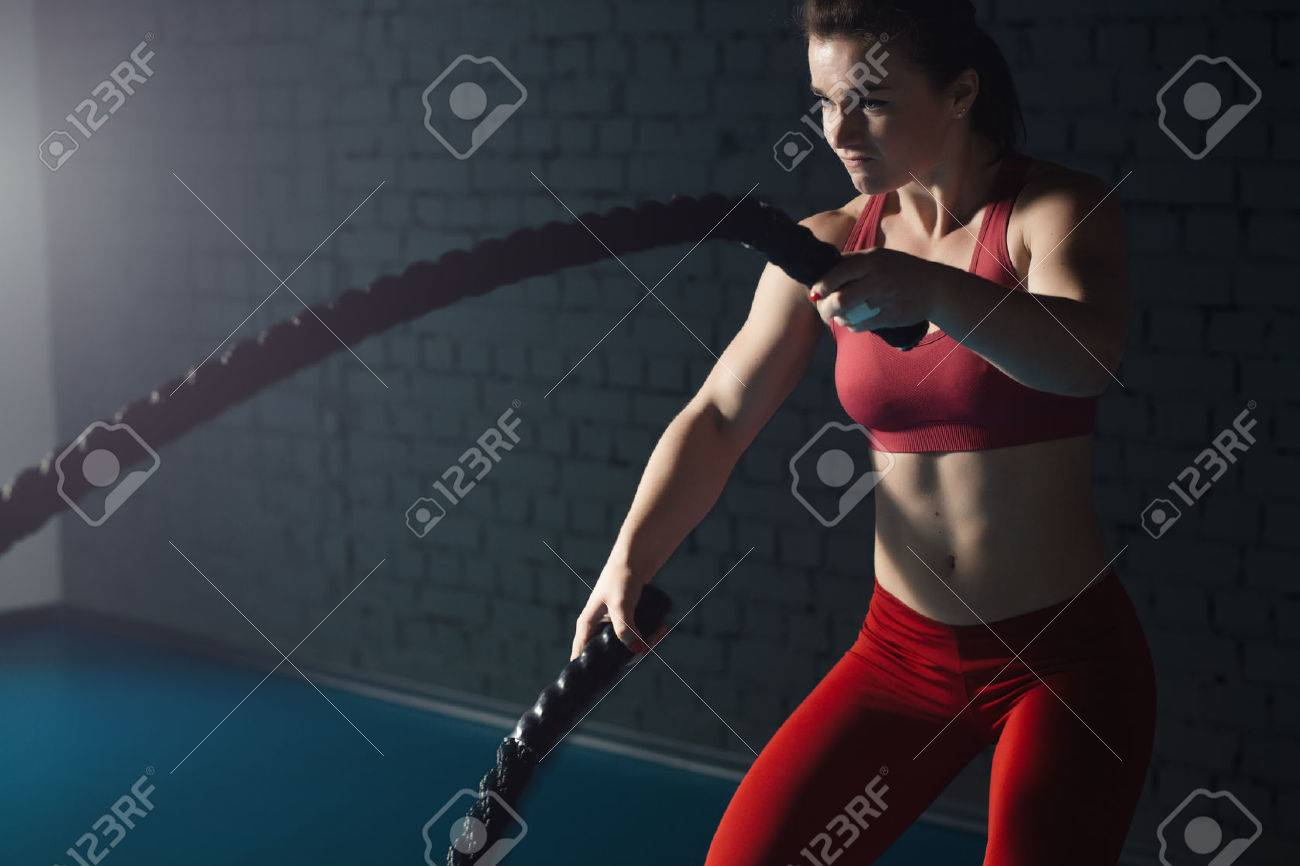 Woman make exercise with battle rope in functional training gym - 75862666