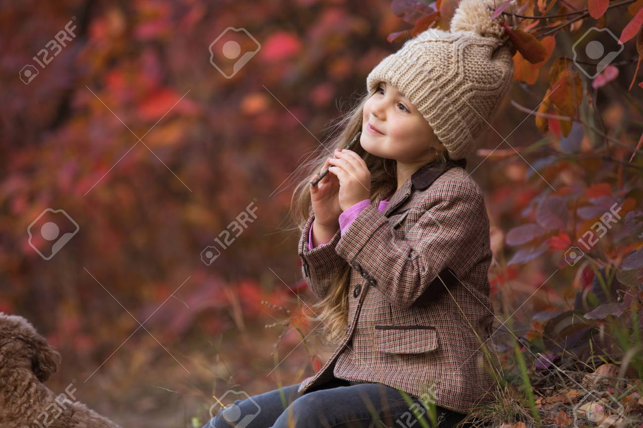 Little girl enjoying autumn day sitting on nature playing sound
