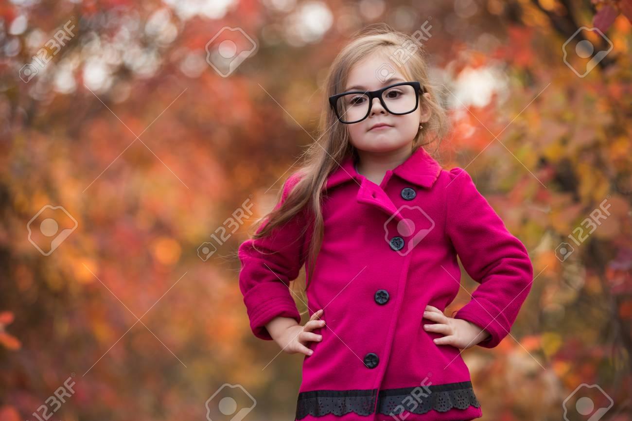 Banque d images - la mode petite fille dans les grandes lunettes de faux à  la journée d automne, le feuillage rouge sur fond 526f39b2bea4