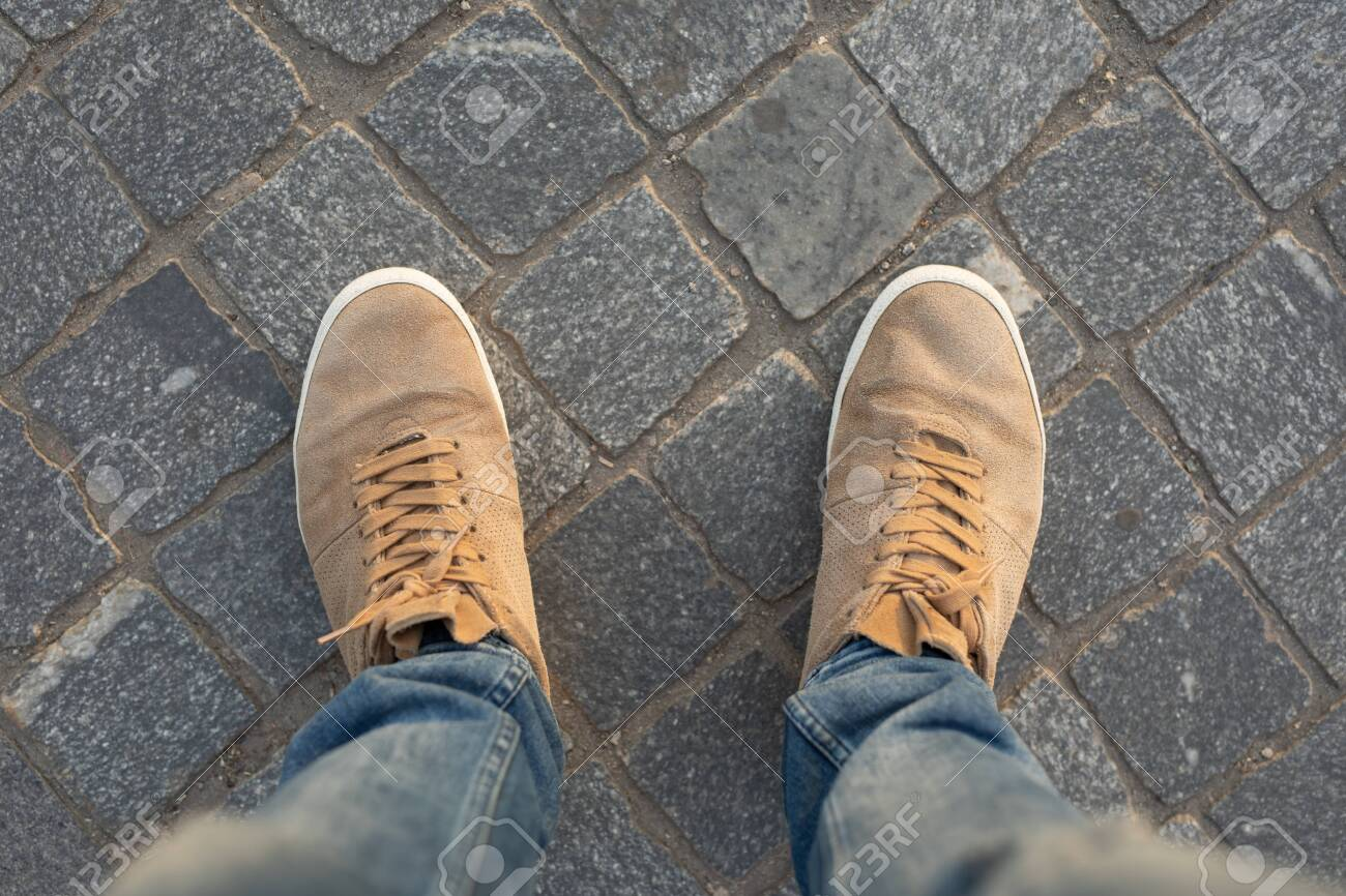 POV of male gumshoes on paving slabs, view from above - 123414701