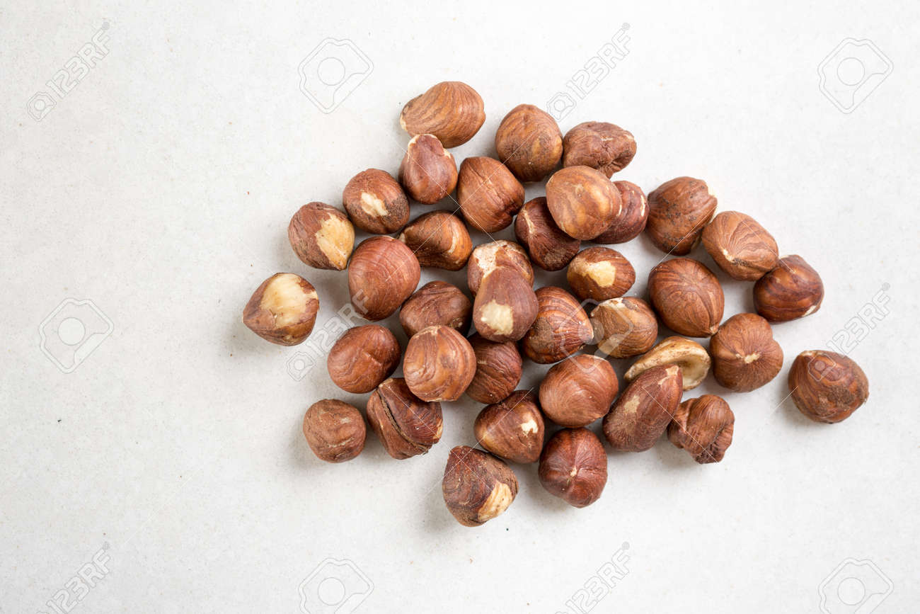Pile of raw hazelnuts isolated above white marble stone. - 145125476