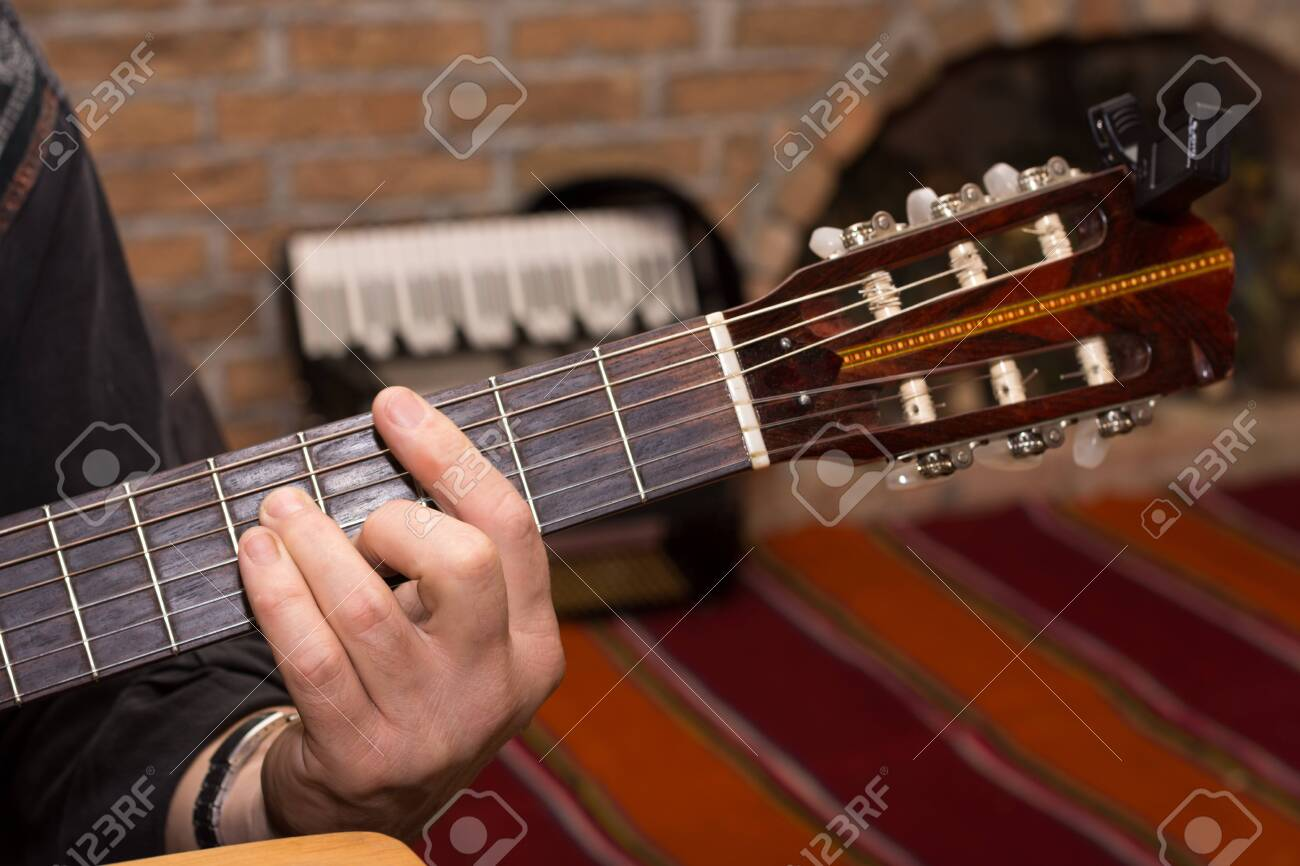 Hand playing chords on the guitar. - 145475835