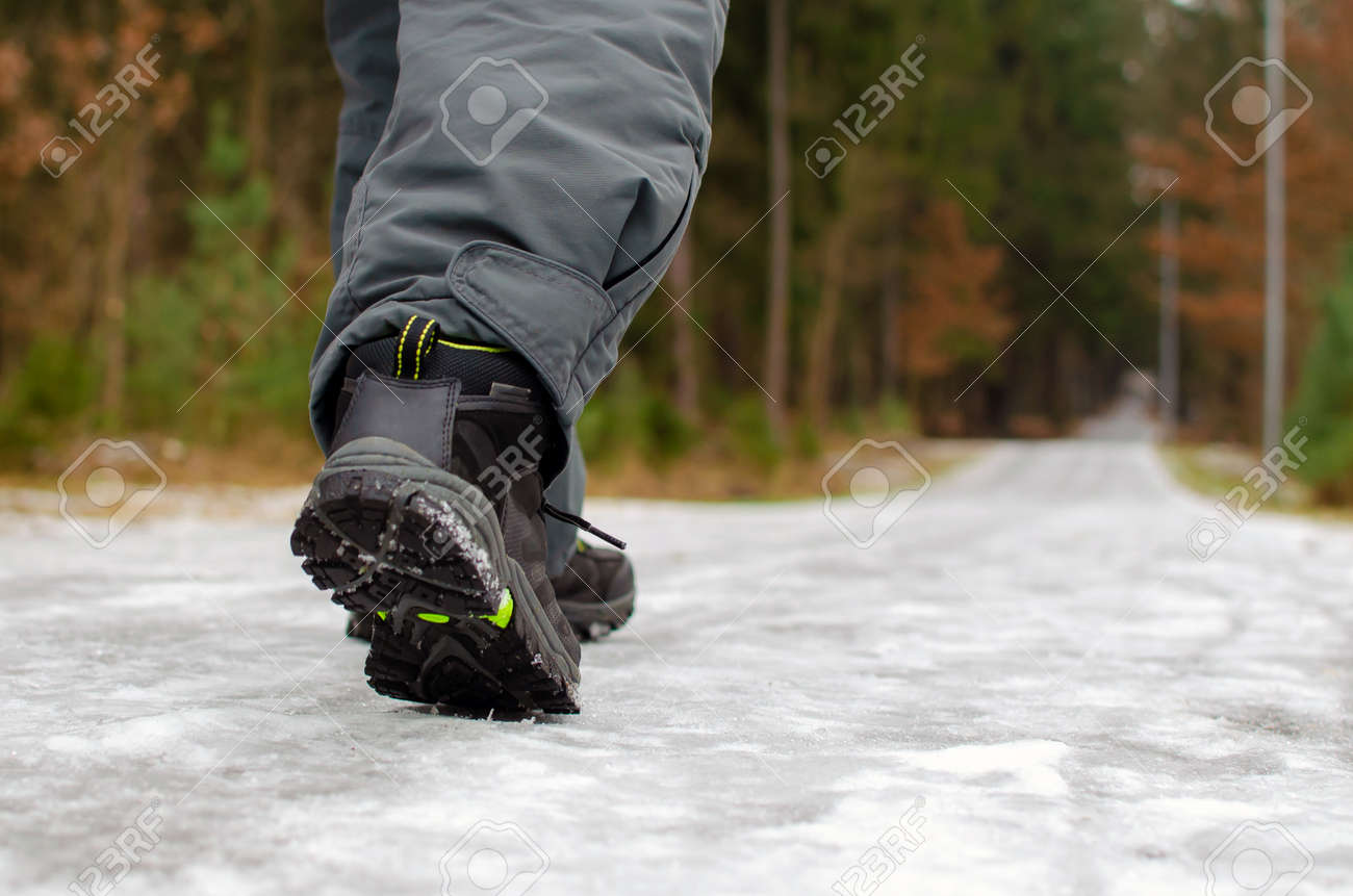 A man walks on a slippery road, the first snow in the park, winter shoes, the road is covered with slippery ice. - 160478255