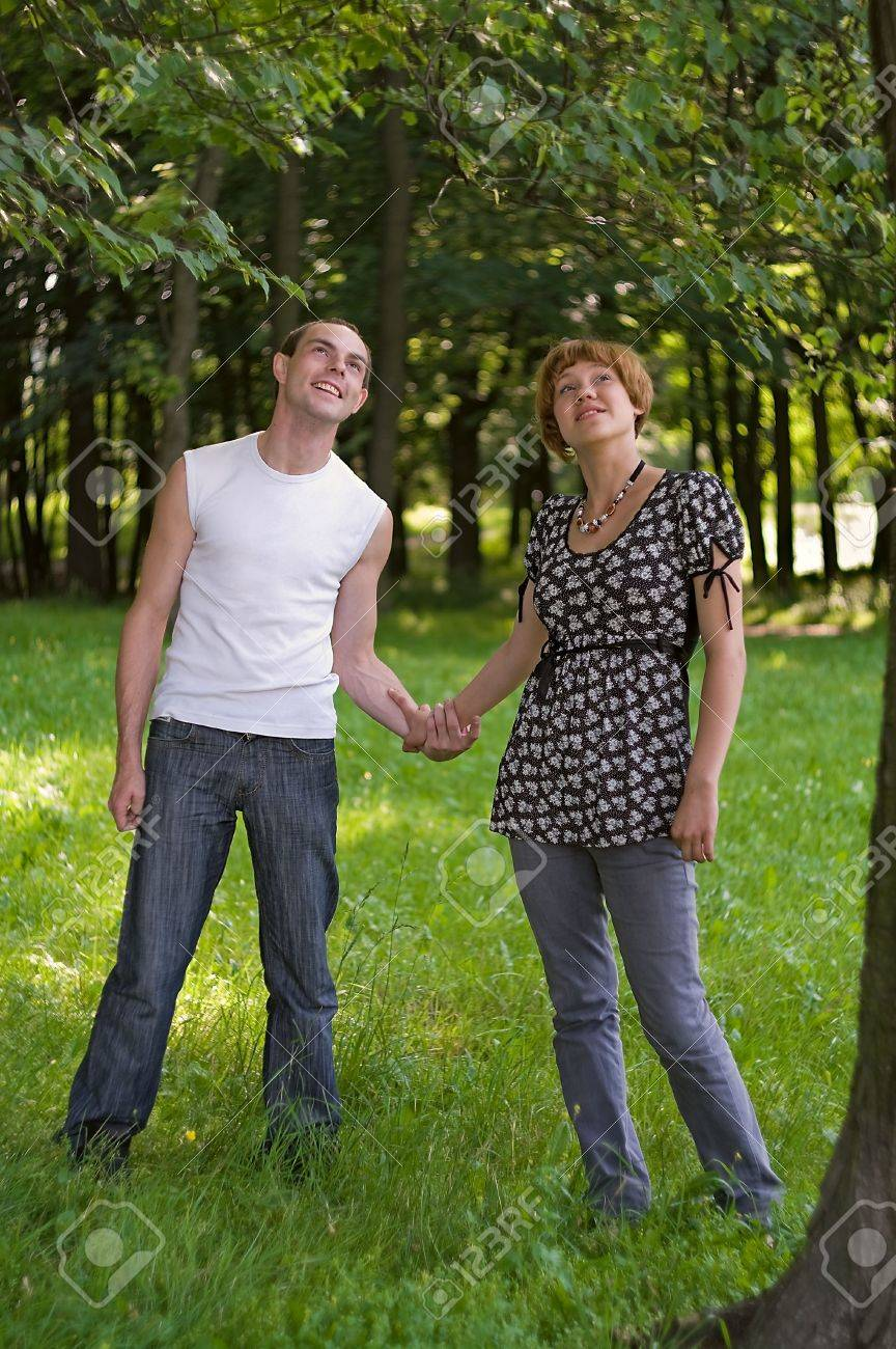Teenagers: man and woman are holding by the hands each other. It is on nature. Full-length portrait Stock Photo - 5254177