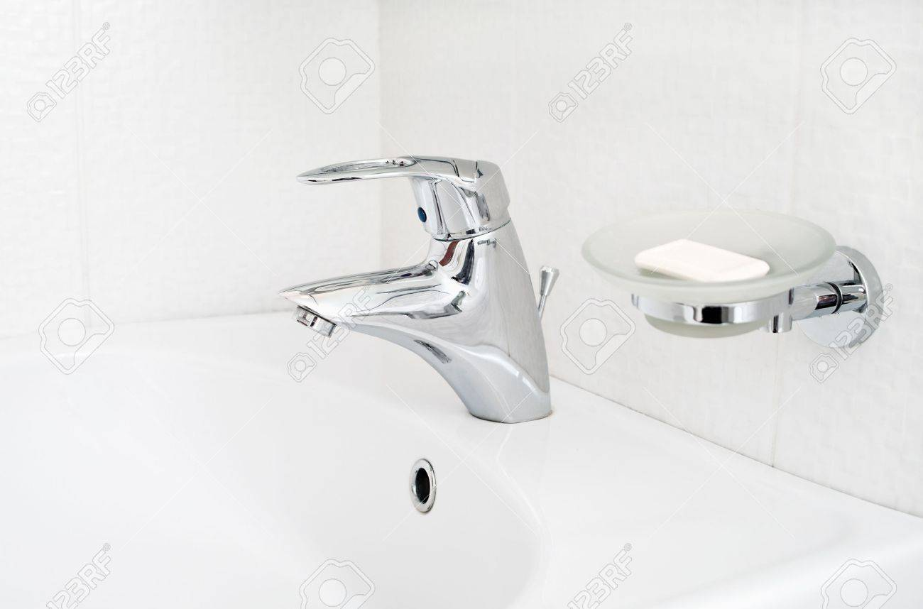 One chrome faucet in washbowl in bath room o white pile with soap holder Stock Photo - 6748028