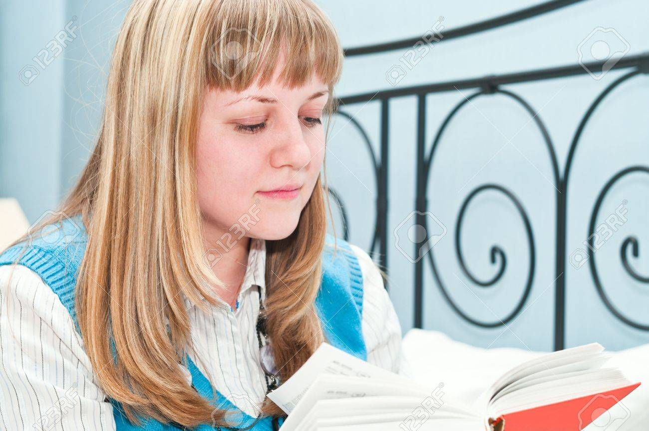 The girl the blonde reads the book lying on a bed Stock Photo - 6866064