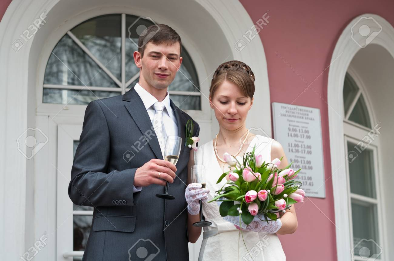 Bride and groom standing near registry office with glasses of champagne. Caucasians. Young wedding couple Stock Photo - 7135178