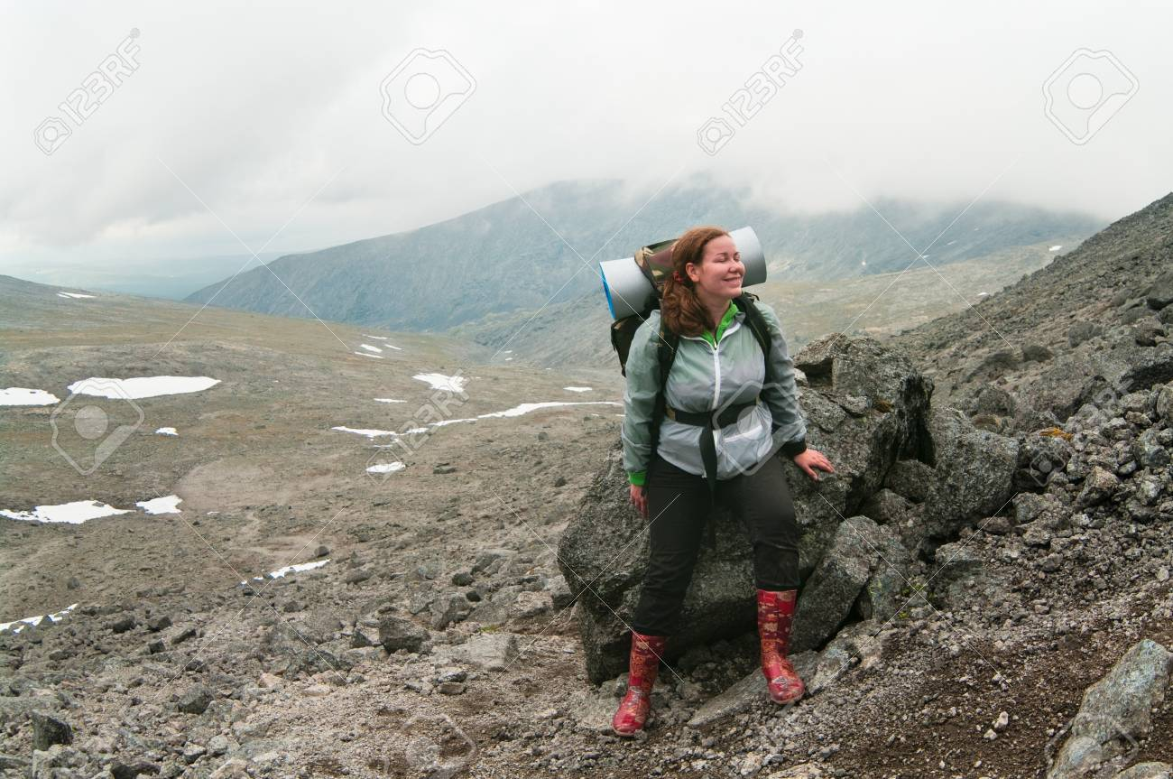 Backpacker a young woman sitting on rock in mountains Stock Photo - 7935617