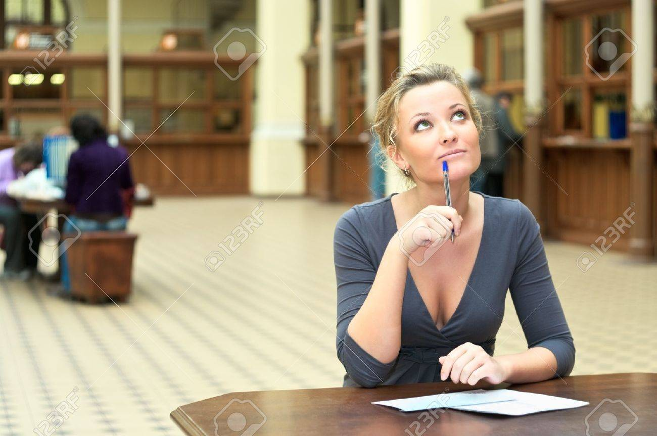 Young beautiful girl sitting at the table thinks. Pen in hand. Copy space Stock Photo - 8780297