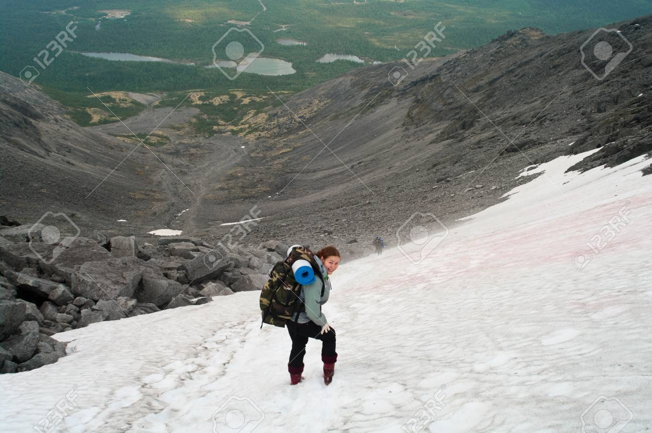 Backpacker a young woman standing on snow in mountains Stock Photo - 9023506