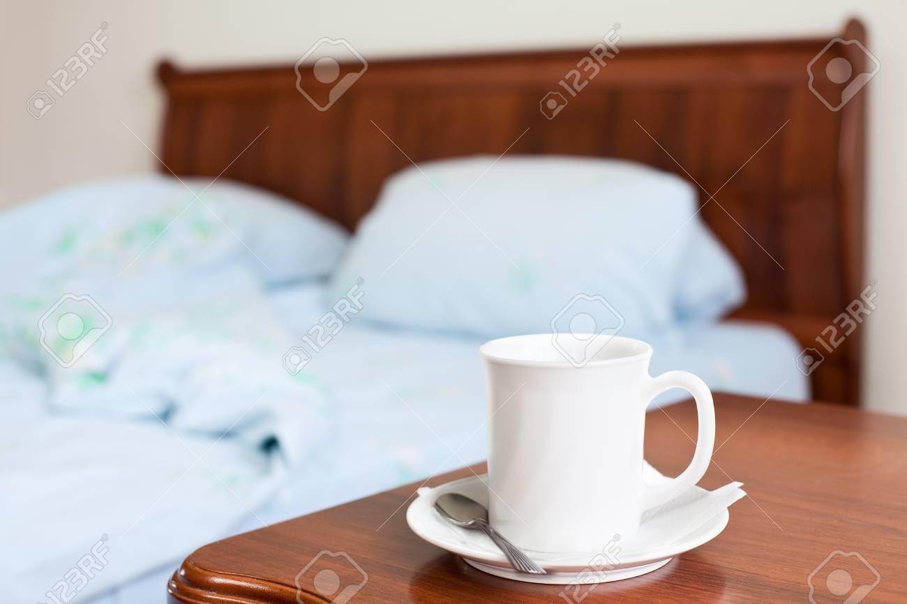 White cup on a bedside nightstand in the bedroom Stock Photo - 9925468