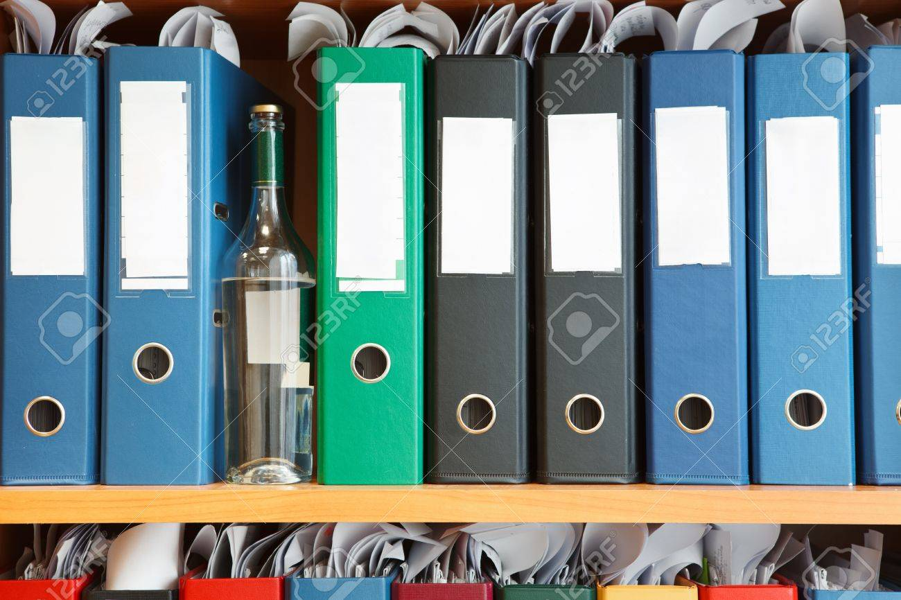 Glass bottle with alcohol hidden between file binders on shelves Stock Photo - 12761194