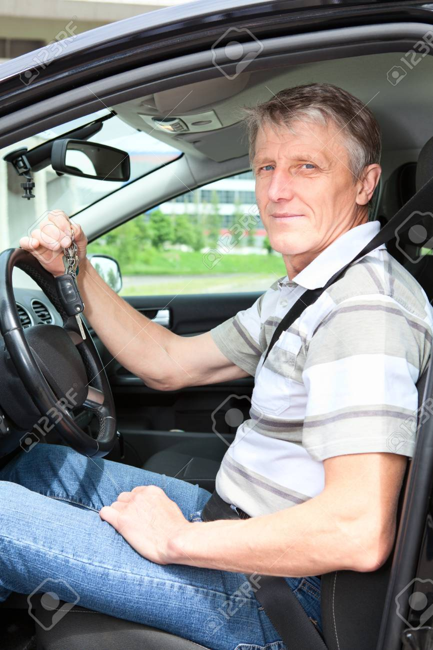 Happy mature driver with car key sitting in own land vehicle Stock Photo - 14386030
