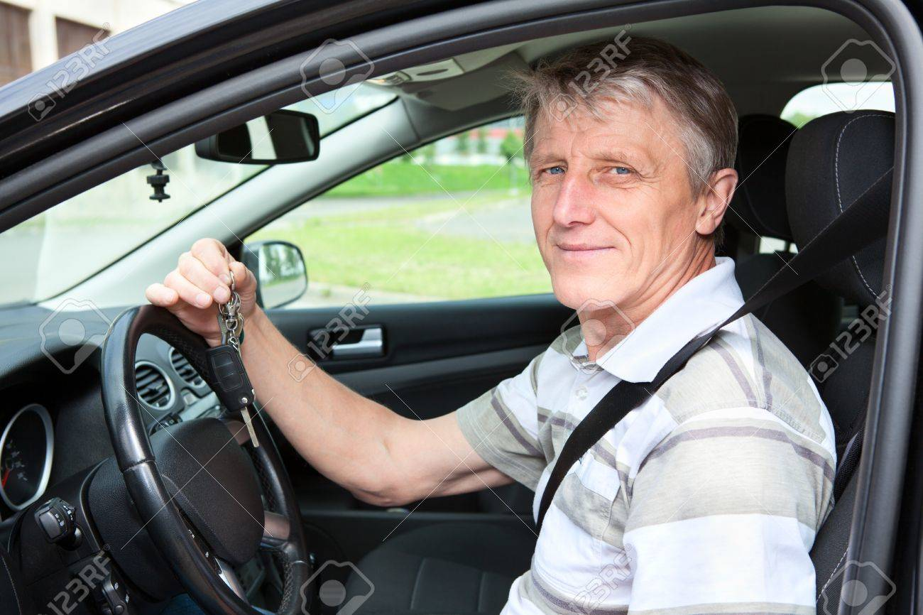 Happy mature driver with car key sitting in own car Stock Photo - 14386020