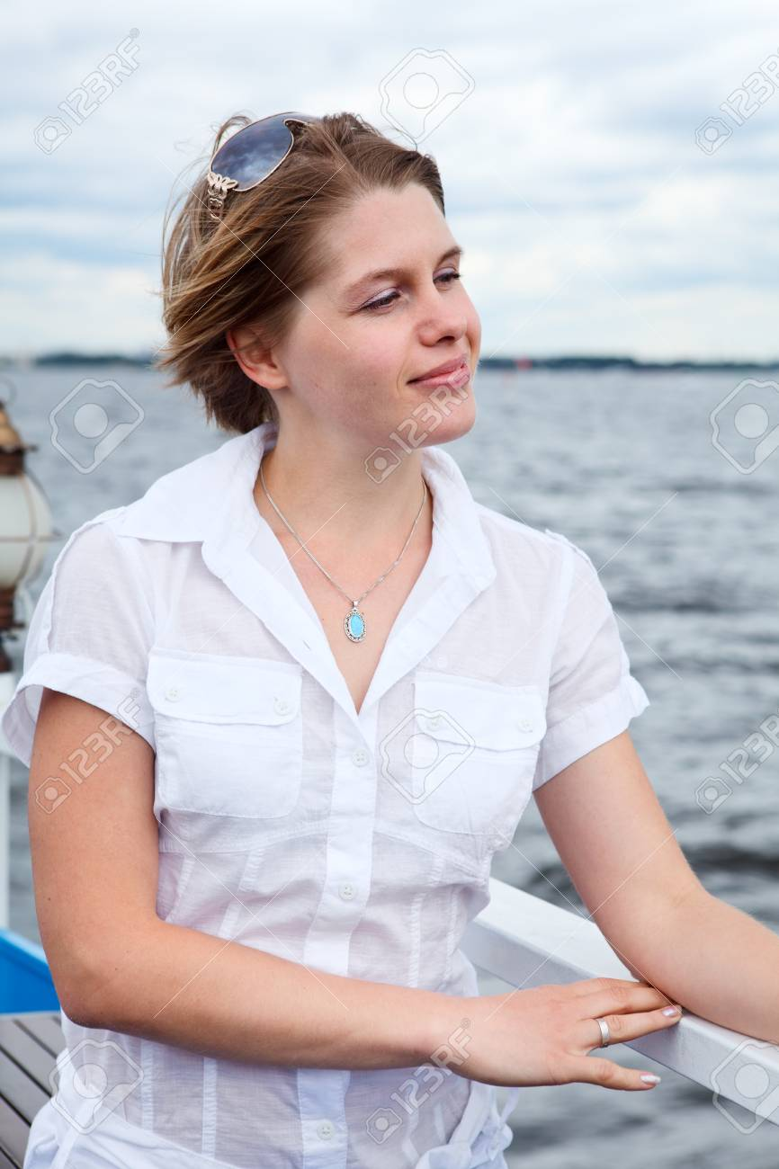 f71b6e93d991 Stock Photo - Woman in white shirt with sunglasses standing on vessel deck  near rails