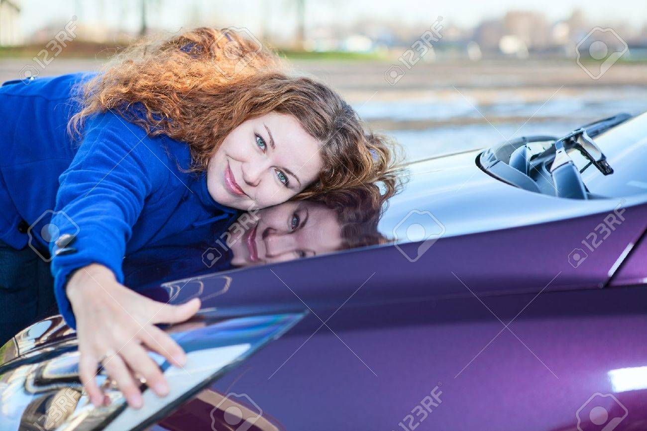 Young female driver embracing hood of new car Stock Photo - 16639447