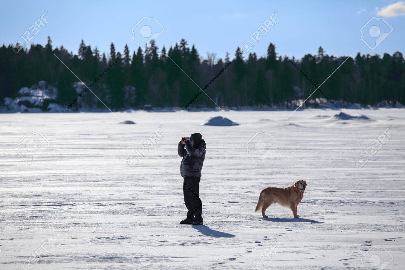 Man with dog looking at binocular and standing on frozen lake Stock Photo - 18787815
