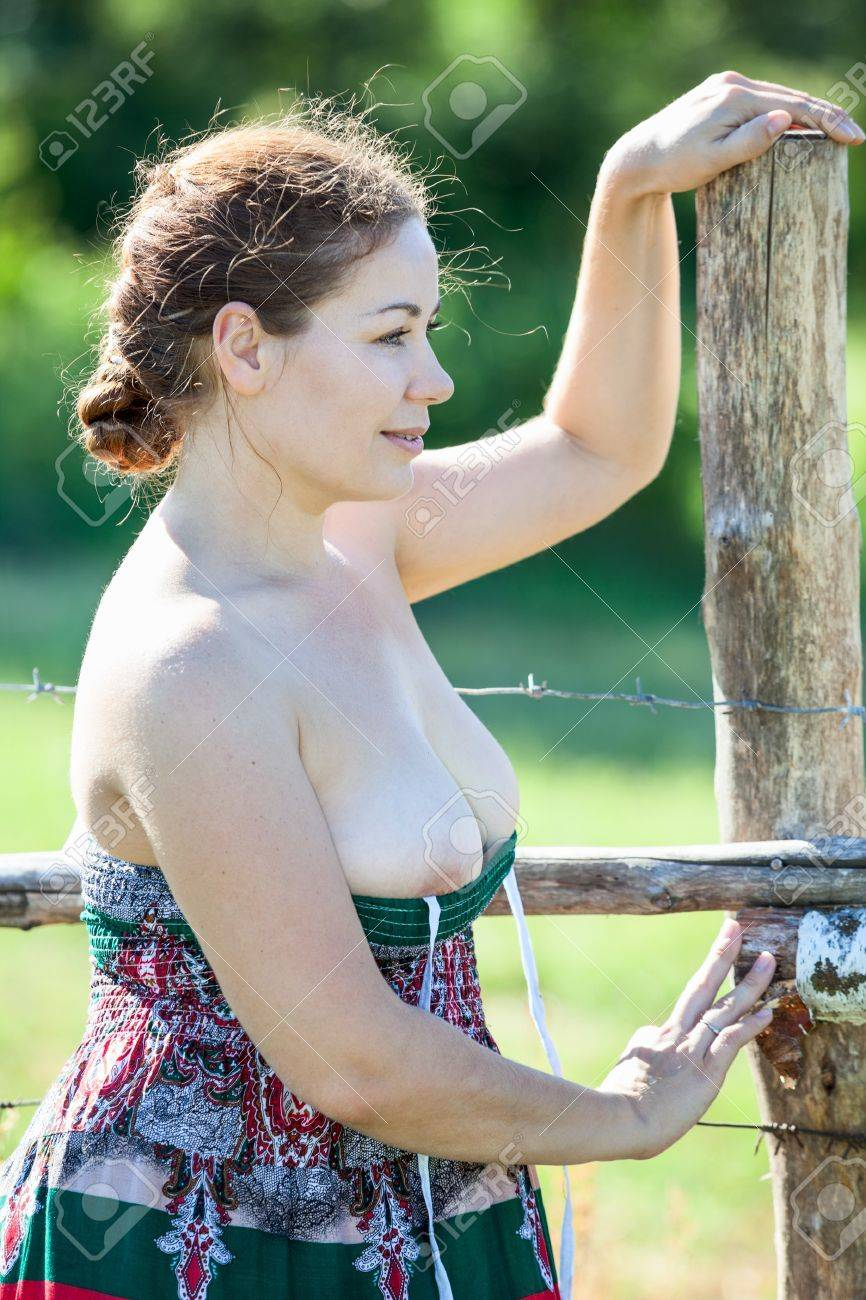 woman in sundress with uncovered breast standing outdoor near