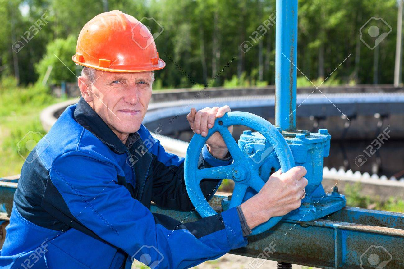 Mature manual worker turning stop-gate valve at factory Stock Photo - 21976730