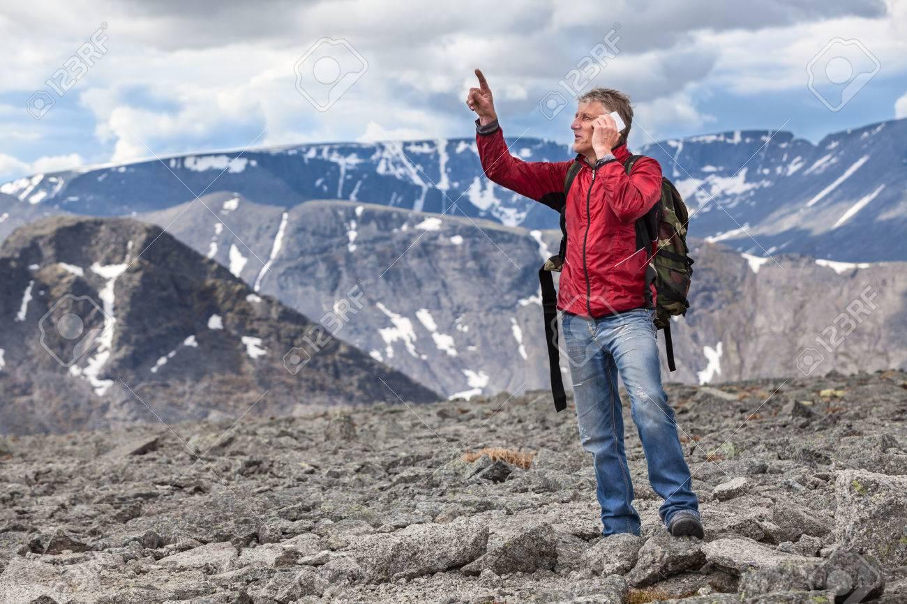 Banque d images - Randonneur de race blanche d âge mûr un homme montre au  sommet de la montagne, de parler sur un téléphone cellulaire 84e9ae0f953