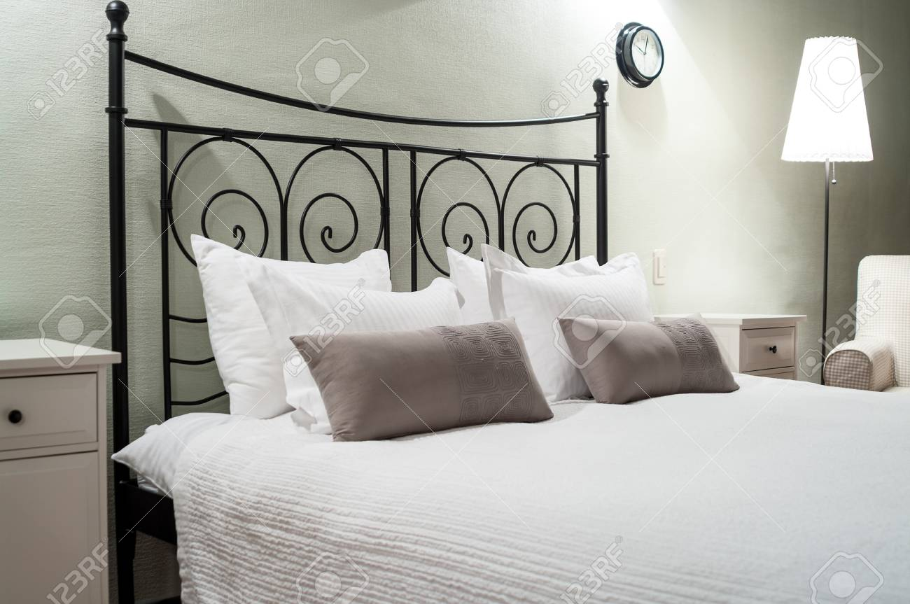 Black Forged Bed With Several Pillows And White Linen Bedside Table