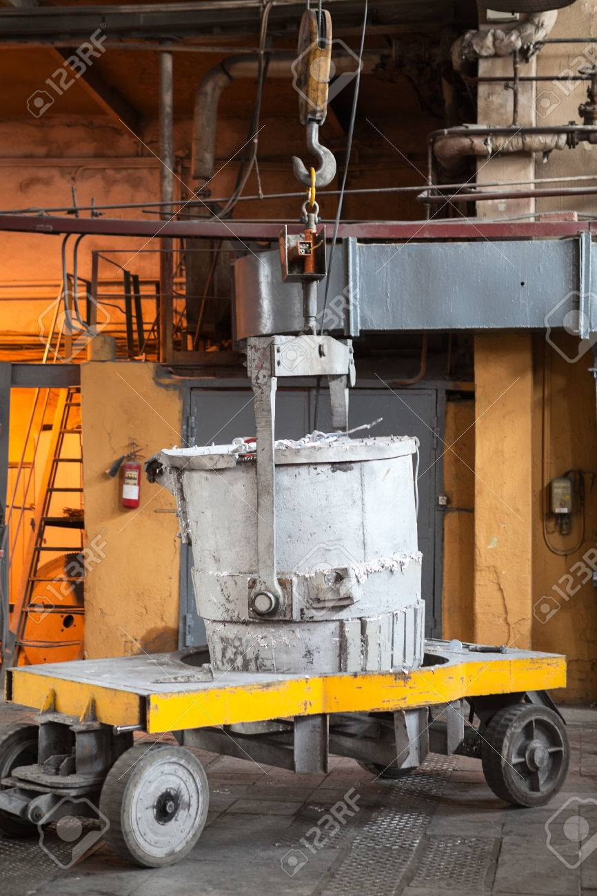 Bucket with molten aluminum stands on trolley to transport it