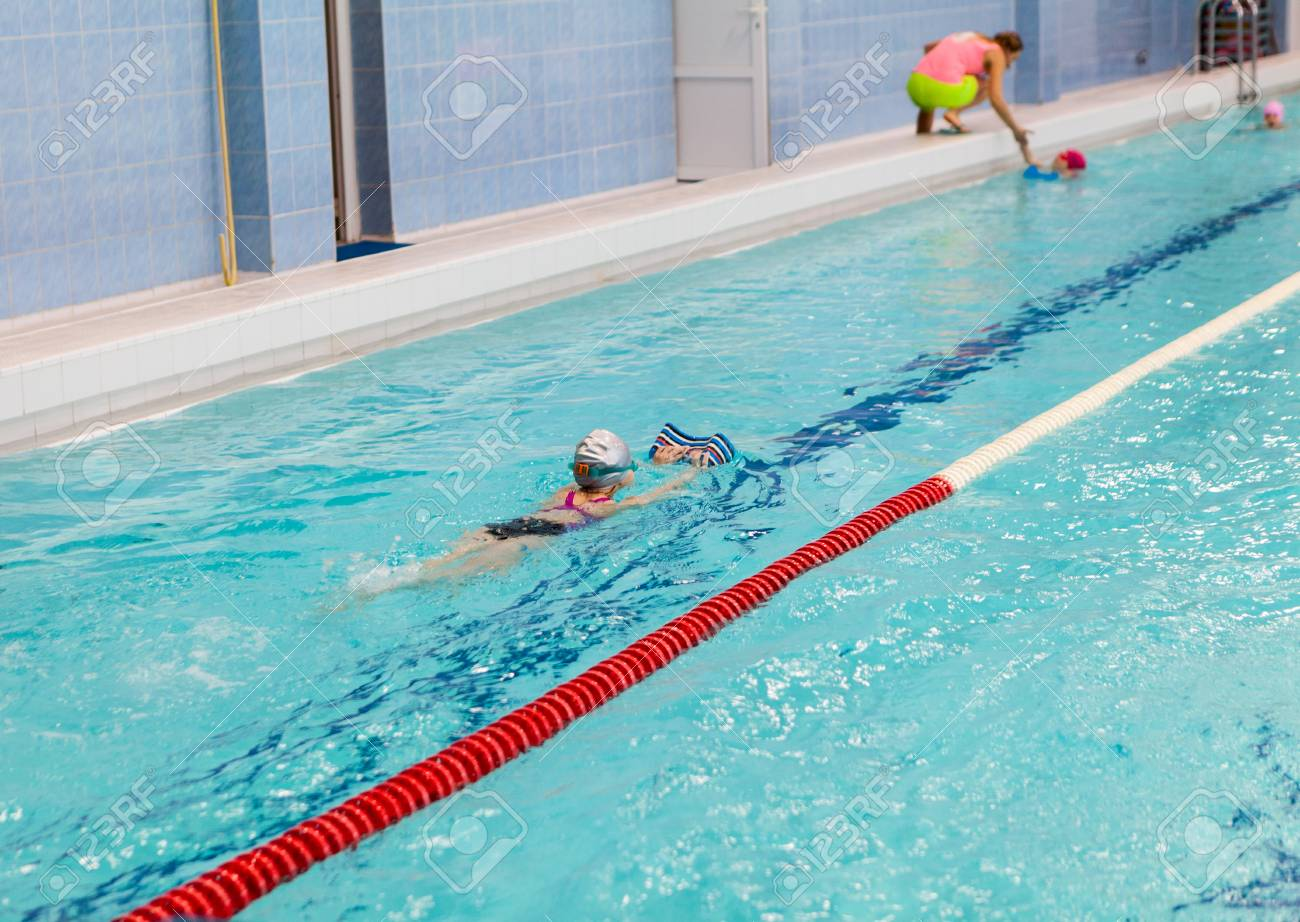 School age girl swims in pool with board. Young children swimming..