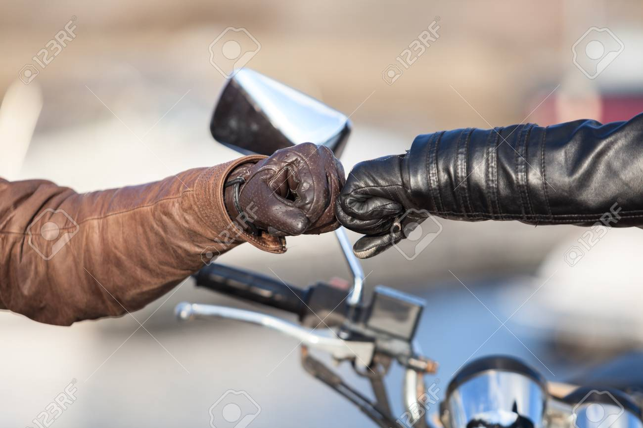 Arms of bikers touching with fists for greeting gesture, close-up view - 101108258