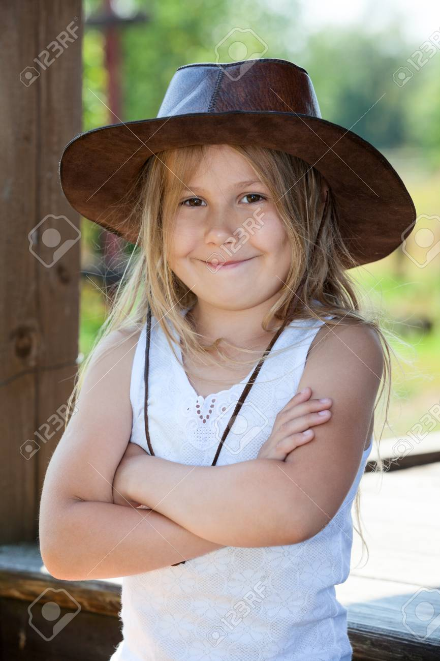 18bc410f3531f Pretty Caucasian girl standing with crossing hands with leather cowboy hat  on her head Stock Photo