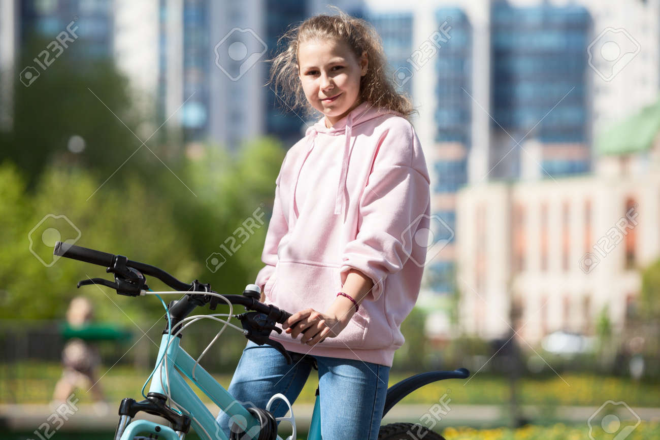 Blond Caucasian teenage girl sitting on her blue bicycle, portrait outdoor - 166844622