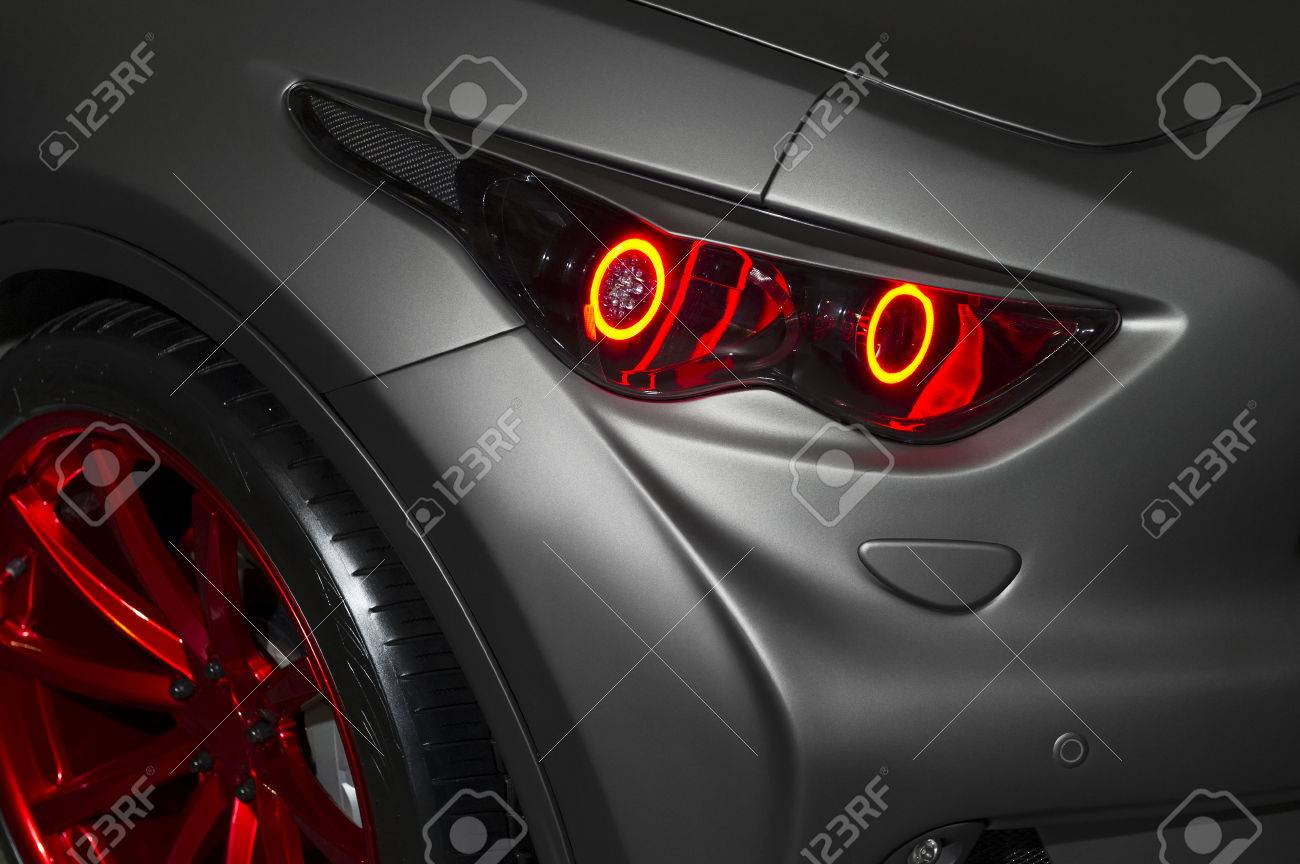 predatory car headlight with red lights and hood of powerful stock