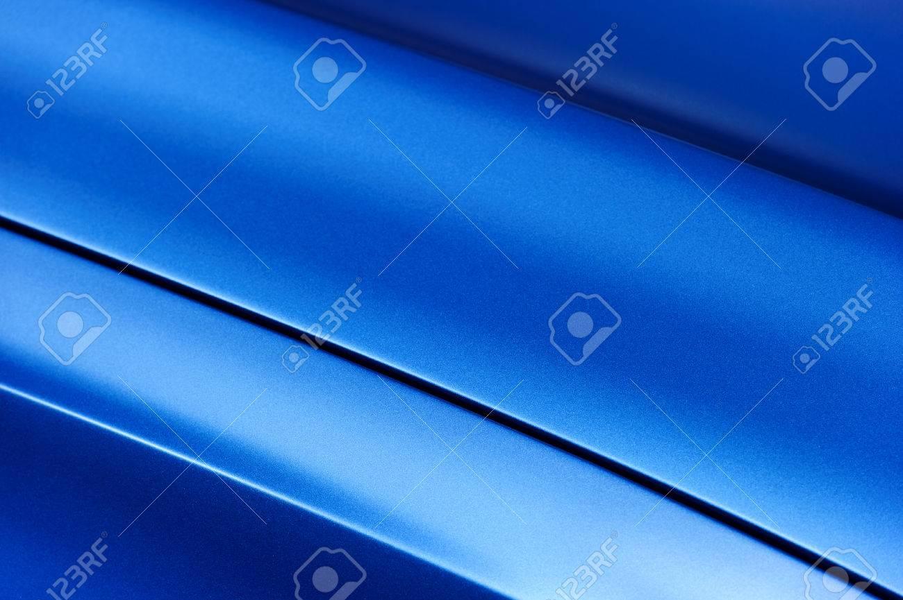Surface of blue sport sedan car metal hood, part of vehicle bodywork, steel gradient line pattern, selective focus - 69895625