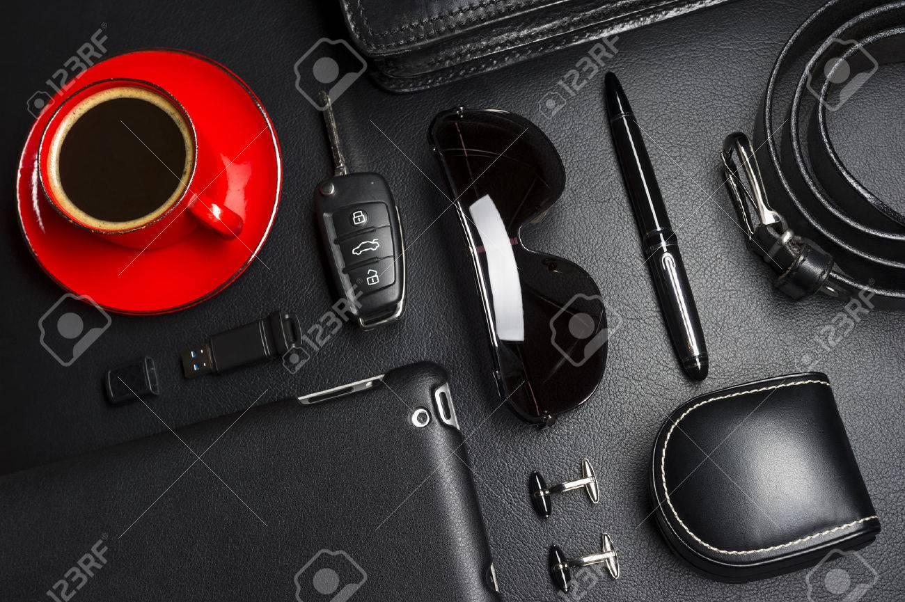 Accesorios de hombre en estilo de negocios con taza de café, gadgets, llave de coche, gemelos, gafas de sol, maletín y otros atributos de empresario