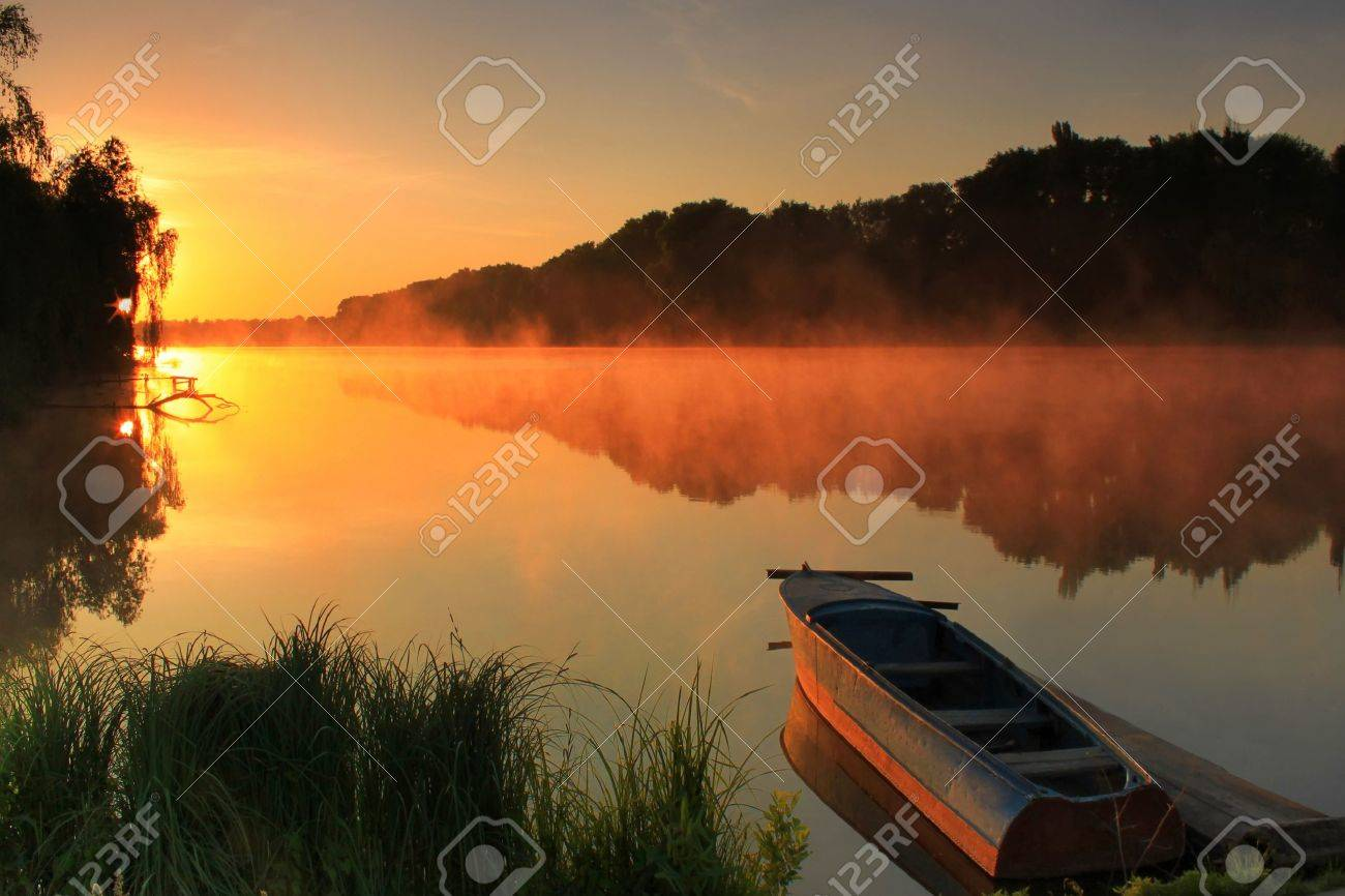 Boat on the shore of a misty lake on a summer morning Stock Photo - 8969351
