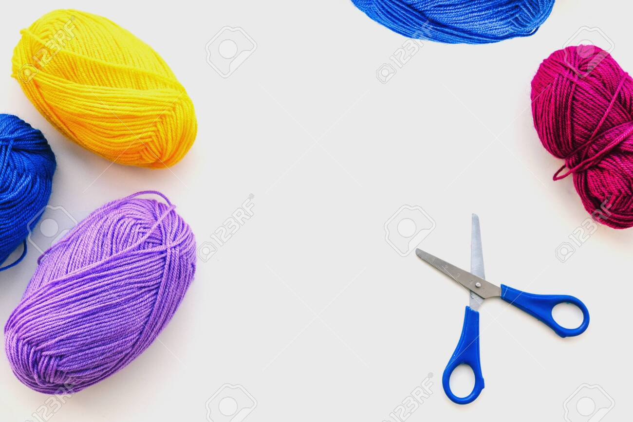 Balls of thread for knitting and scissors. Knitting threads on a white background. Multi-colored balls of thread for needlework. Copy space. Handmade concept - 130643824