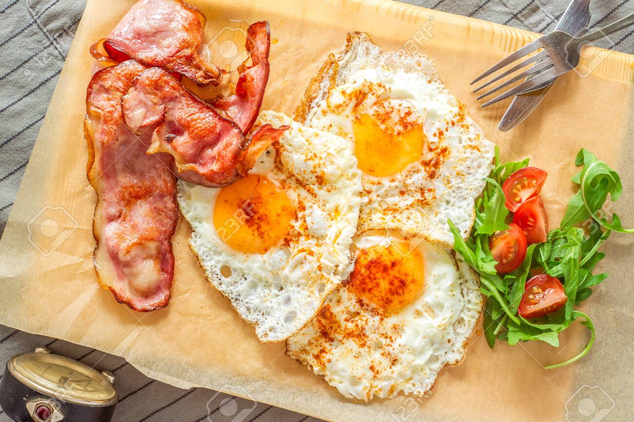 English breakfast with ham and eggs served on a wooden plate. - 146379017