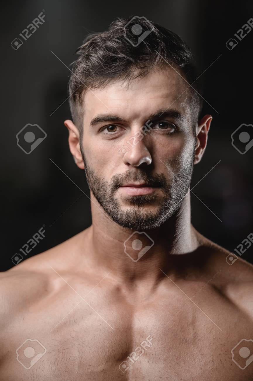 Handsome men face close up portrait in the gym fitness strength training workout bodybuilding concept background