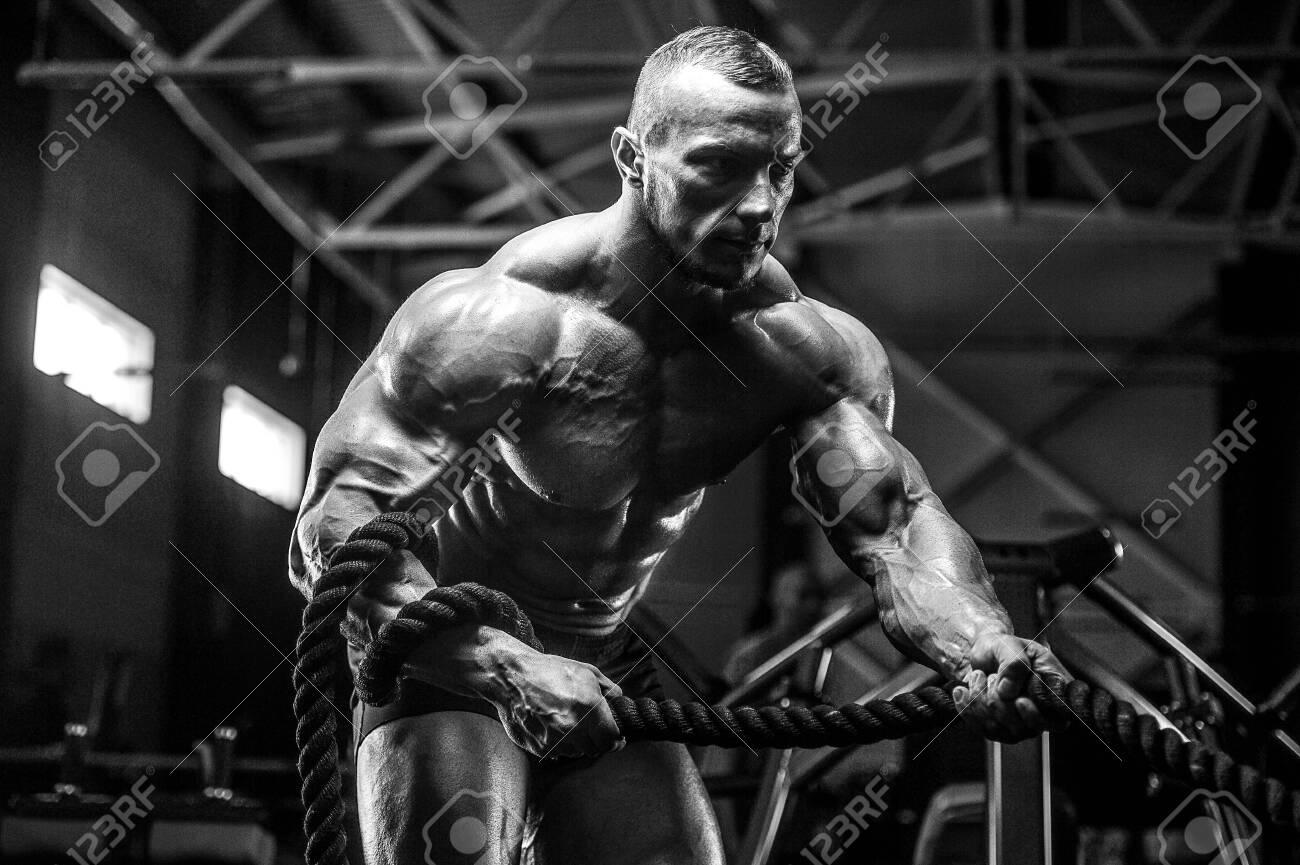 Brutal strong athletic men pumping up muscles workout bodybuilding concept background - muscular bodybuilder handsome men doing exercises in gym torso - 129556638
