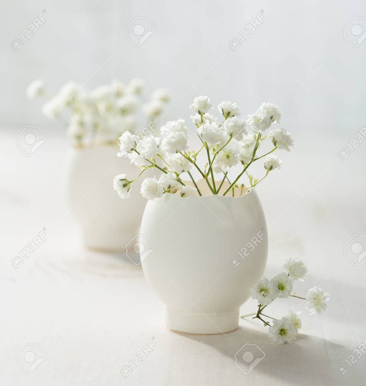 Bunch of white flowers gypsophila in eggs shell on the white bunch of white flowers gypsophila in eggs shell on the white wooden plank mightylinksfo